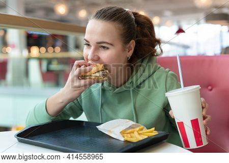 Beautiful Hungry Girl With Appetite Bites, Eats Juicy Big Delicious Burger, Hamburger, French Fries,