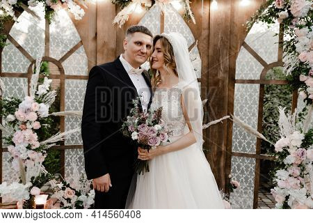 A Young And Happy Newlywed Couple Stand In Front Of A Wooden Arch Decorated With Flowers And Differe