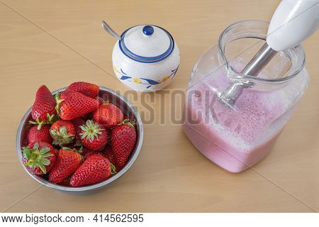 Bowl Full Of Strawberries And A Pitcher With Freshly Made Strawberry Milkshake, A Sugar Bowl, A Hand