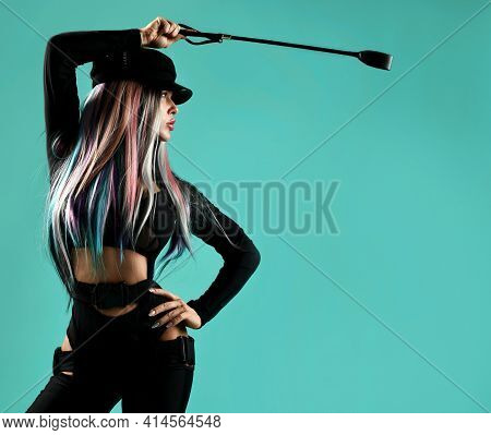 Young Blonde Woman With Colored Strands In Black Leather Sexy Costume Standing Holding Whip In Hand