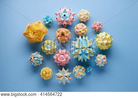 Set Of Multicolor Handmade Modular Origami Balls Or Kusudama Isolated On Blue Background. Visual Art