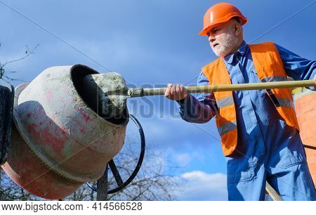 Construction Worker Works With Concrete Mixer. Cement Creation. Builder Prepares Cement Mortar.