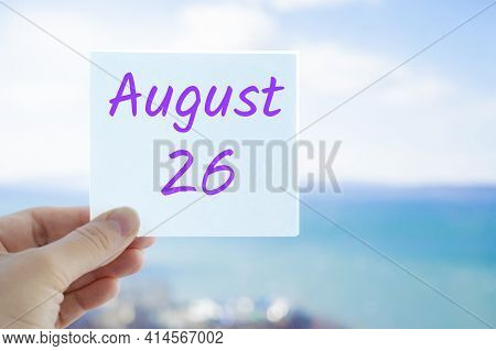 August 26th. Hand Holding Sticker With Text August 15 On The Blurred Background Of The Sea And Sky.