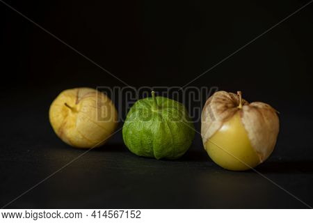 Three Tomatillos Lined Up On Black Background, Viewed From Dinner Angle- California Produce Concept
