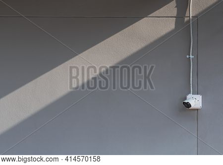 Security Camera With Flexible Metal Conduit On Gray Cement Wall Outside Of Building