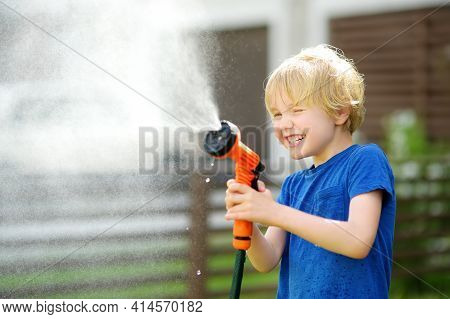 Funny Little Boy Watering Lawn And Playing With Garden Hose With Sprinkler In Sunny Backyard. Presch