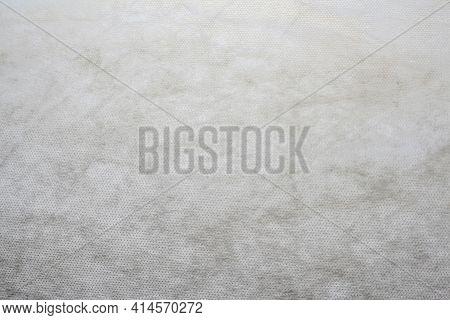 Defocus Grey Spunbond Non-woven Geotextile Close-up Macro. White Surface. Close Up. Small Spots. Dir