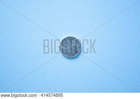 Coin One Rouble On Bright Blue Background. Ruble Depreciation. Rouble To Dollar