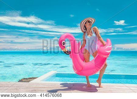 Summer pool fun swimsuit model posing in pink flamingo float showing off slim figure bikini ready body for luxury Caribbean vacation getaway. Woman having fun by hotel infinity pool.