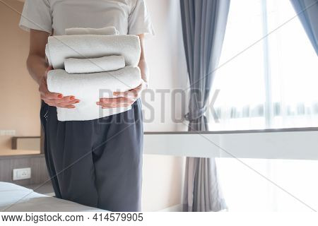 Cropped Shot Of Hotel Maid Holding The Stack Of Towels In Hotel Bedroom. Conceptual Of Female Chambe