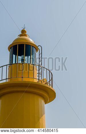 Top Of Yellow Lighthouse Against Hazy Overcast Sky.