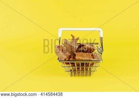 Shopping Basket With Dog Treats On A Yellow Background. Natural Dried Chew Treats For Pets. Pieces O