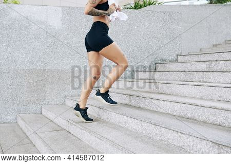 Cropped Image Of Fit Young Woman With Towel In Hands Running Up The Stairs