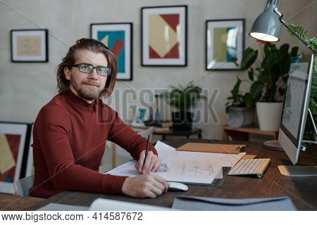 Happy young bearded male architect in eyeglasses and casualwear looking at you while sitting by table in front of camera and working over sketch
