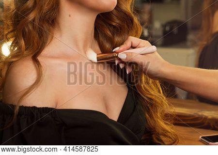 Makeup Preparation Process. Professional Makeup Artist Works With Brush On Model Neck And Chest In B