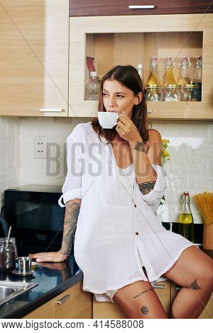 Pretty Young Woman In Loungewear Drinking Morning Coffee And Looking Away When Sitting On Kitchen Co