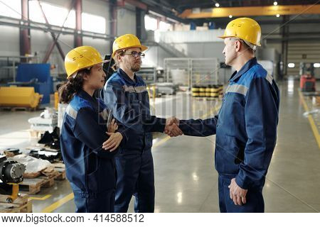 Two male engineers in hardhats and workwear greeting one another by handshake in workshop with female colleague standing near by