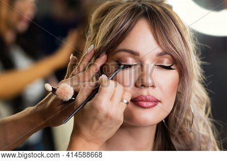 Makeup Artist Applies Eyeliner. Beautiful Woman Face. Hand Visagiste. Make Up Process. Female Eye Wi