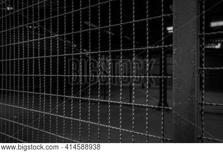Metal Wire Fence Of Empty Warehouse. Dark Background Of Private Area. Steel Fence Wall For Security.