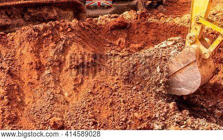 Backhoe Digging Soil At Construction Site. Bucket Of Backhoe Digging Soil. Crawler Excavator Digging