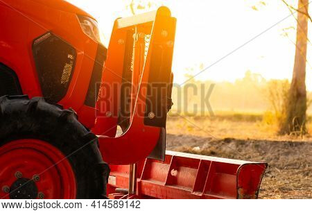 Orange Tractor Parked At Rice Farm In Summer Morning With Sunlight. Agricultural Machinery In Agricu