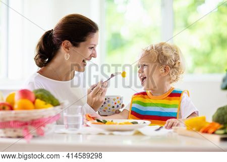 Mother Feeding Child Vegetables. Mom Feeds Kid In White Kitchen With Window. Baby Boy Sitting In Hig