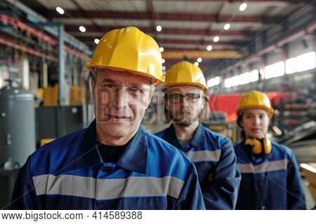 Mature male worker of large industrial plant or factory or foreman in workwear and protective helmet standing against two colleagues