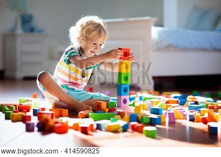 Child Playing With Colorful Toy Blocks. Kids Play. Little Boy Building Tower Of Block Toys Sitting O