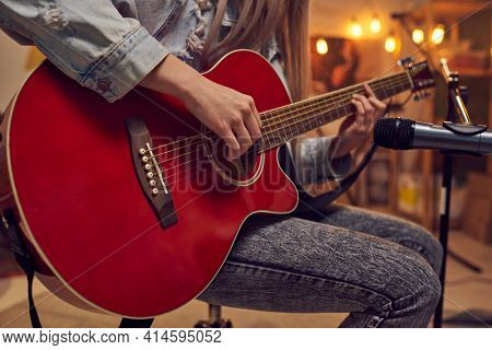 Close-up of young female musician sitting in front of microphone and playing guitar during performance