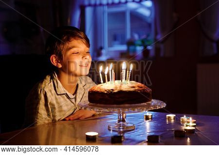 Adorable Happy Blond Little Kid Boy Celebrating His Birthday. Child Blowing Candles On Homemade Bake