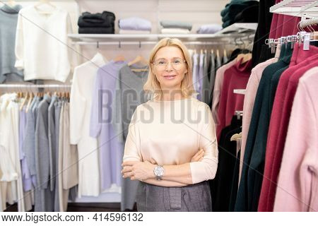 Portrait of mature beautiful saleswoman smiling at camera while standing in the clothing store and waiting for customers