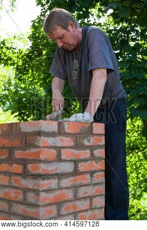 Senior Man Is Making A Chimney Of Red Bricks, Working With A Trowel And Making Masonry Works On A Ro