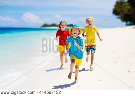 Kids Playing On Beach. Children Play At Sea.