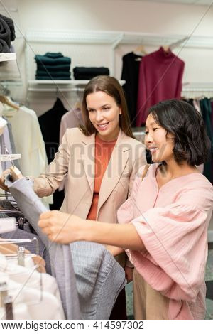 Young smiling saleswoman helping customer to choode the right dress in clothing store