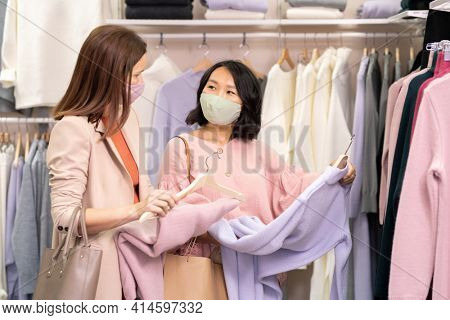Two beautiful friends in masks choosing jumpers and dresses together during their shopping in clothing store