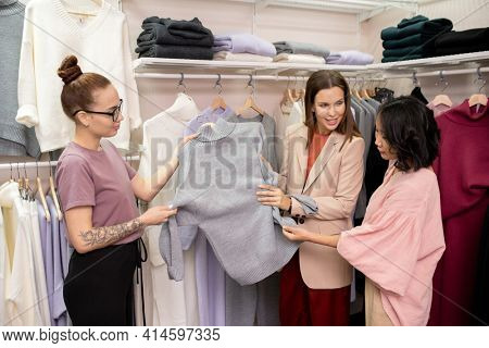 Two saleswomen suggesting new jumper to the customer during shopping in clothing store