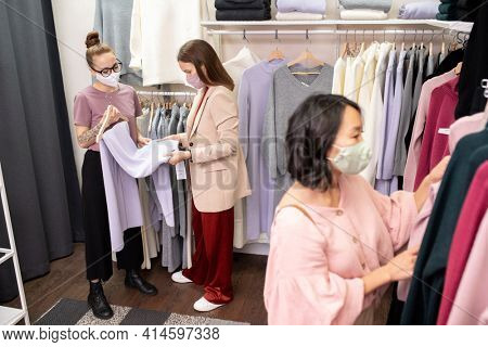 Young women in protective masks doing shopping in store during pandemic