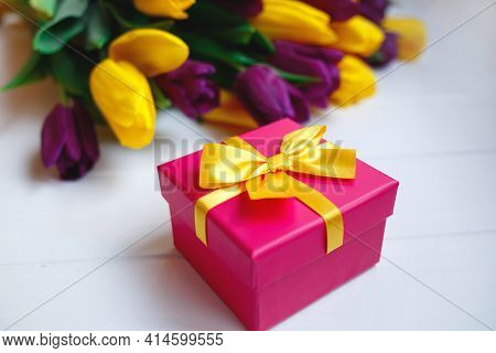 Pink Gift Box With Yellow Bow On The Background Of A Bouquet Of Tulips