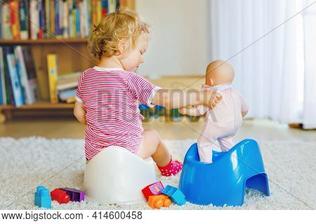 Closeup Of Cute Little 12 Months Old Toddler Baby Girl Child Sitting On Potty. Kid Playing With Doll