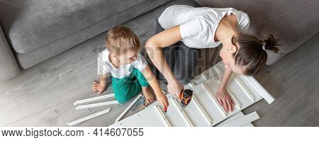 Cute Adorable Caucasian Toddler Boy Kid Sit On Floor And Help Mom Assembling Furniture Shelf With Po