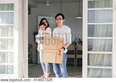 An Asian Man Smiled Happily While Carrying The Box To Move Into A New Home. With His Wife Carrying C