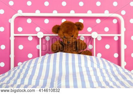 Pink girly bedroom with teddy bear sitting on bed