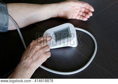 Elderly Woman Measuring The Pressure With Blood Pressure Monitor. Old Age, Health Care And Cardiolog