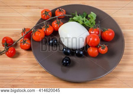 Ball Of Fresh Mozzarella Cheese, That Was Soaked In Whey Among Black Olives, Cherry Tomatoes And Par