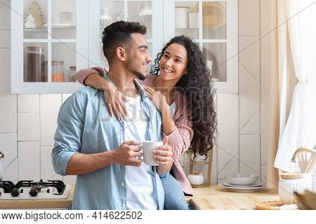 Happy Young Arab Spouses Hugging And Drinking Coffee In Cozy Kitchen Interior