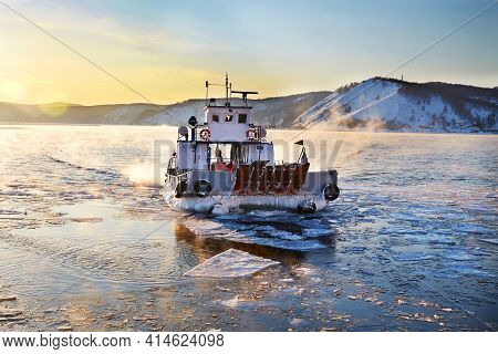 Beautiful Sunset On Lake Baikal In Spring. Melting Ice And Open Water In The Lake. The Ferry Ferries