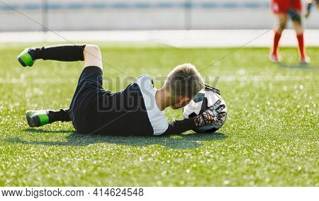 Soccer Goalie Drills. Young Boy As A Soccer Goalkeeper In Action Catching Ball. Football Kid Saving