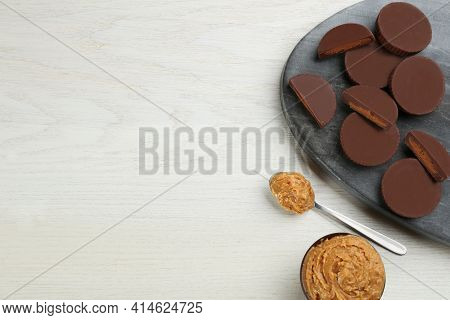Delicious Peanut Butter Cups On White Wooden Table, Flat Lay. Space For Text