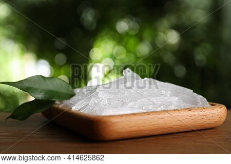 Menthol Crystals And Green Leaves On Wooden Table Against Blurred Background, Closeup