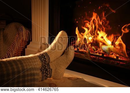 Woman In Knitted Socks Near Fireplace At Home, Closeup